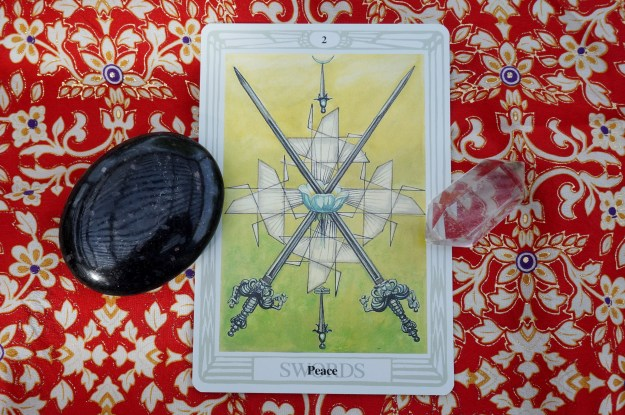 1 tarot card with a black stone and a clear quartz point.
