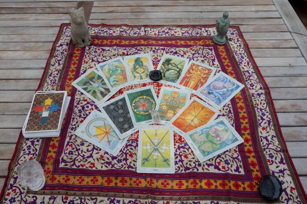 13 tarot cards on a patterned silk scarf.
