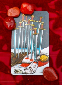 Scorpio: 10 of Swords with sunstone and Red Jasper stones.