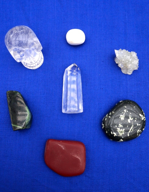 Clockwise from top: Scolecite, Apophyllite, Chinese Writing Rock, Pipestone, jade, quartz skull. Center: Quartz point.