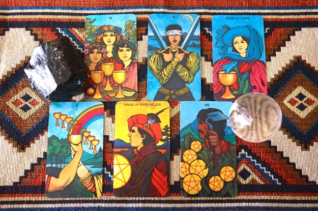 6 tarot cards and 2 crystals on a colorful background.