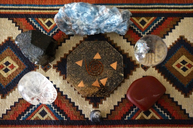 Orgone Generator surrounded by 6 stones (clockwise, starting at 12 o'clock): Blue Calcite, Quartz Sphere, Pipestone, Purpurite, Quartz Skull, Black Tourmaline.
